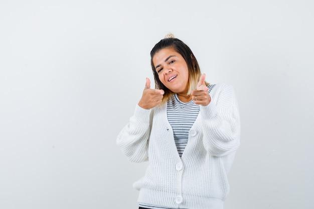 티셔츠를 입은 매력적인 여성, 앞을 가리키고 자랑스러워하는 카디건