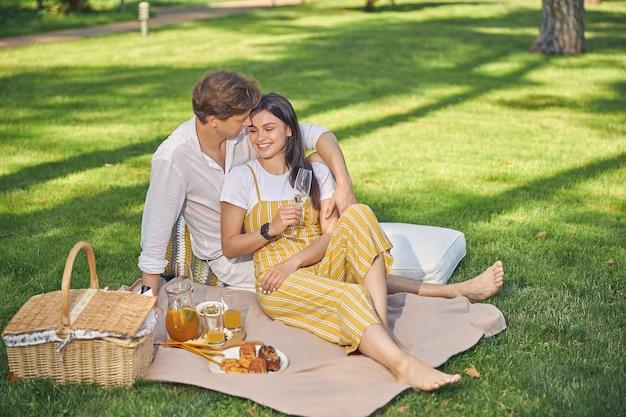 피크닉에서 사랑스러운 남자와 시간을 보내는 노란색 바지에 매력적인 아가씨