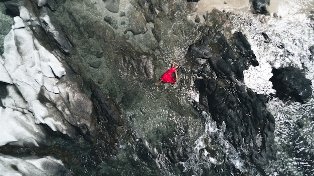Charming lady lying among the rocks in a red dress