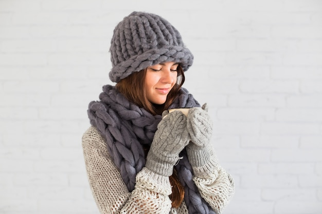 Charming lady in mittens, hat and scarf with cup in hands