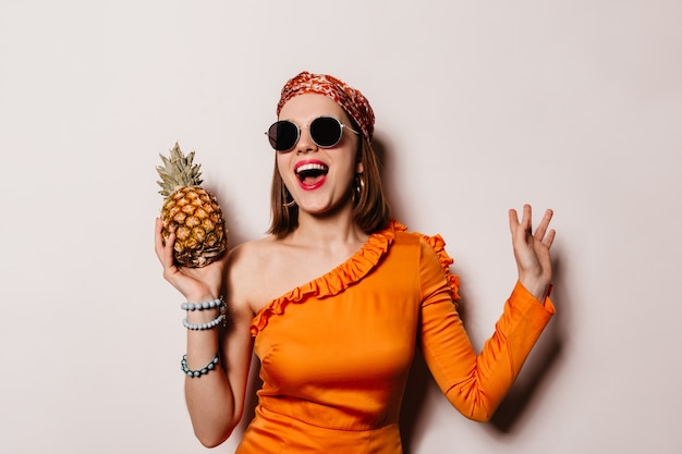 Charming lady in orange blouse, headdress and glasses laughs and holds pineapple on white space.