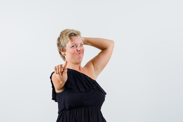 Charming lady pointing at camera while winking in black blouse