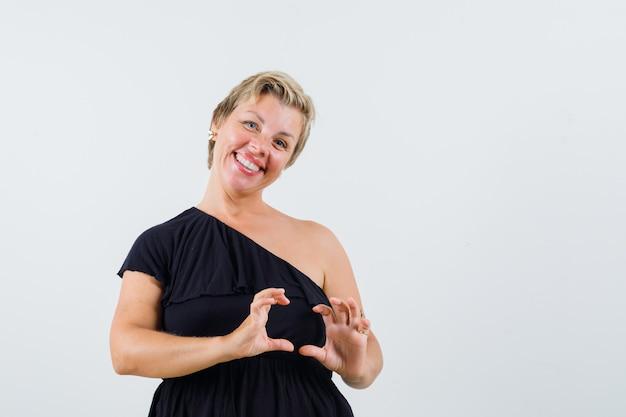Affascinante signora in posa come tenere qualcosa in camicetta nera e sembra soddisfatta