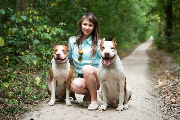 魅力的な女性が屋外の犬と一緒にポーズします。