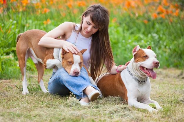 屋外の犬と一緒にポーズをとって魅力的な女性