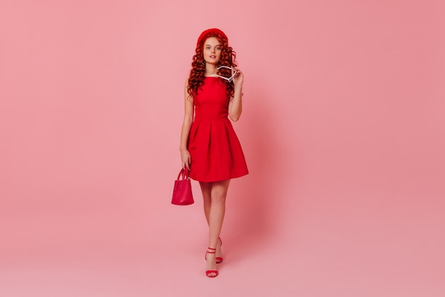 Charming lady in red mini dress, holding mini handbag and white glasses. curly redhead girl in beret posing on pink space.