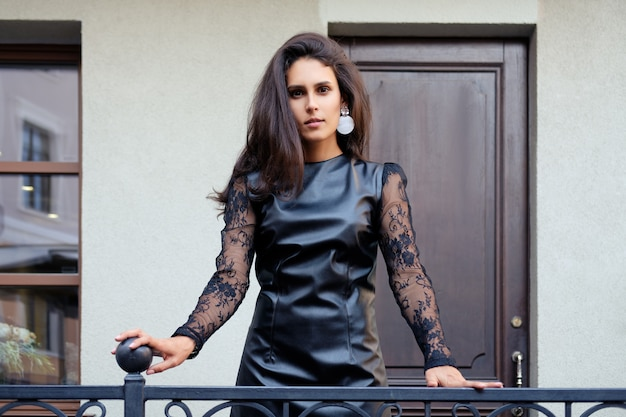 Charming lady in short leather dress with lace sleeves outdoor