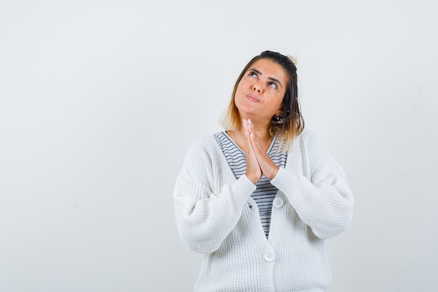 Affascinante signora che mostra le mani giunte in gesto di preghiera in t-shirt, cardigan e sembra speranzosa