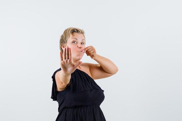 Affascinante signora che mostra il gesto della chiusura lampo mentre mostra il gesto di arresto in camicetta nera e sembra riluttante. vista frontale.