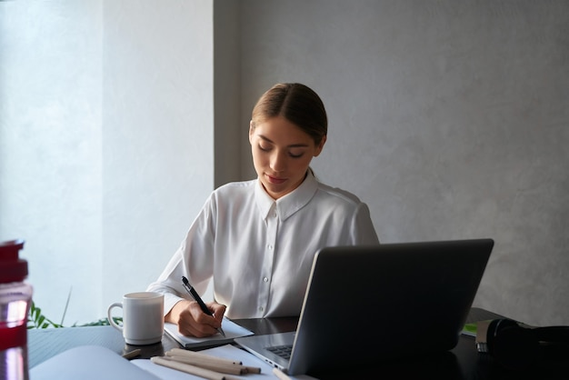Очаровательная дама сидит за столом и использует беспроводной ноутбук