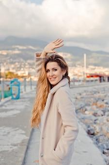 昼間に海辺に立って手を振っている魅力的な女性