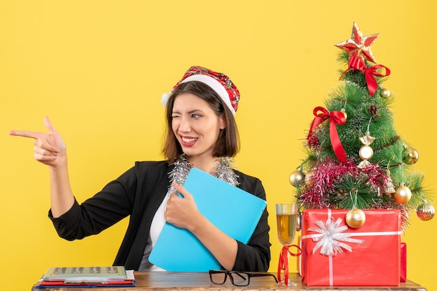 Charming lady in suit with santa claus hat and new year decorations holding document making funny reactions in the office on yellow isolated