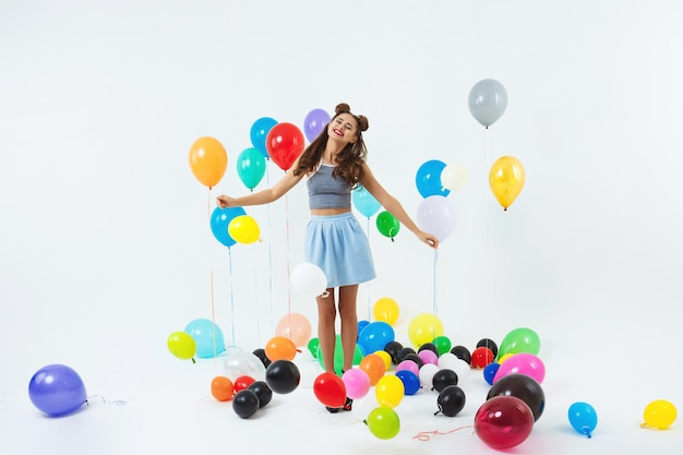 Charming lady in trendy clothing looks happy holding balloon bunch