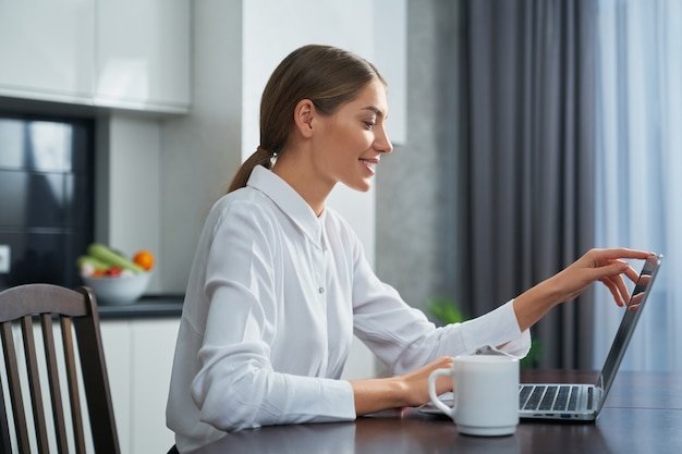 Charming lady using laptop for video conversation