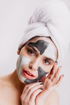 Очаровательная дама с черно-белой маской для сужения пор позирует на белой стене. фотография женщины в полотенце на голове с милой улыбкой