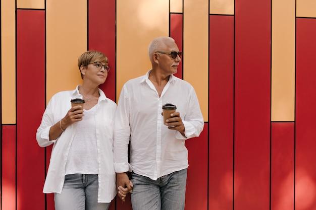 Affascinante signora con i capelli corti freschi in occhiali e camicetta fresca che tiene una tazza di tè e posa con l'uomo con i baffi su rosso e arancione.