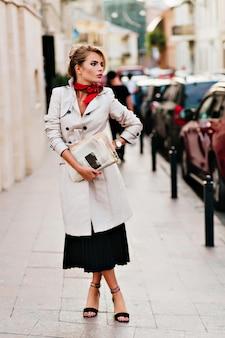 Affascinante signora con acconciatura elegante in attesa di qualcuno per strada e guardandosi intorno