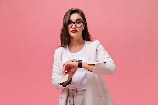 분홍색 배경에 포즈 붉은 입술으로 매력적인 아가씨. 흰색 양복과 안경에 심각한 젊은 여자 격리 된 배경에서 카메라를 살펴 봅니다.