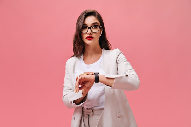 Affascinante signora con labbra rosse in posa su sfondo rosa. la giovane donna seria in vestito e occhiali bianchi esamina la macchina fotografica sul contesto isolato.