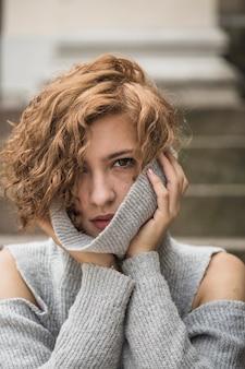 스웨터의 칼라를 들고 짧은 곱슬 머리를 가진 매력적인 아가씨
