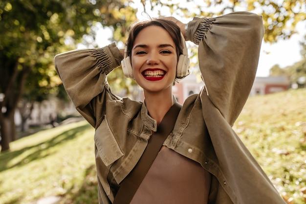 야외에서 진심으로 웃고있는 데님 긴 소매 재킷에 짧은 머리를 가진 매력적인 아가씨. 밝은 입술 헤드폰에서 젊은 여자는 외부 포즈.