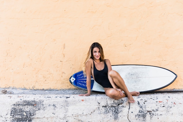 Charming lady with surfboard sitting near building