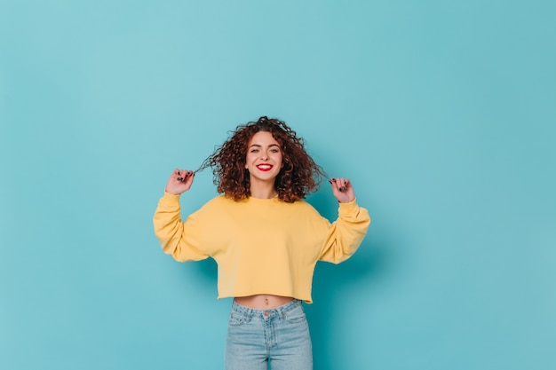 Charming lady in yellow sweater and skinny jeans smiles and touches her curly dark hair against blue space.