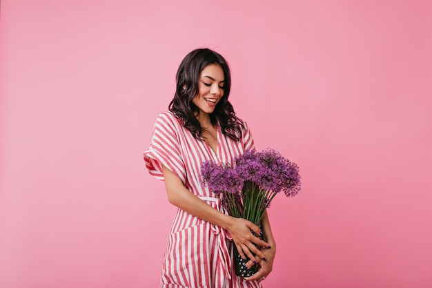 Charming latin woman with affection looks at bouquet of purple wild flowers. girl in striped dress embarrassed posing.