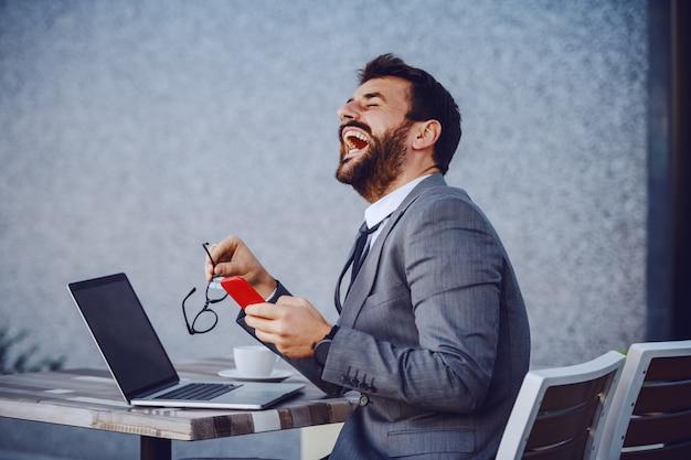カフェに座っている間スマートフォンを使用してスーツで魅力的な笑い白人のひげを生やした実業家。テーブルの上にはノートパソコンとコーヒーがあります。
