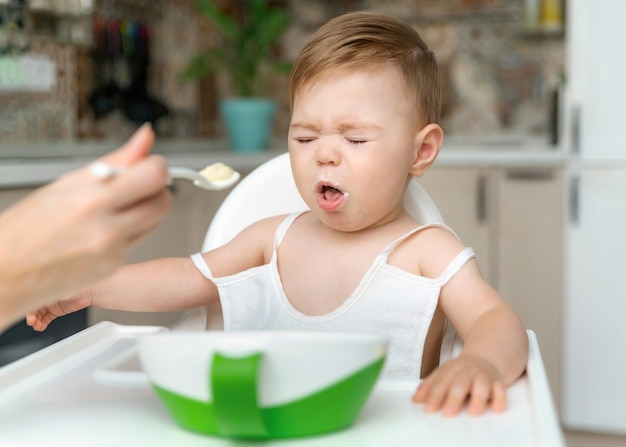 Charming little baby boy 811 months doesnt want to eat porridge from spoon with mom at home