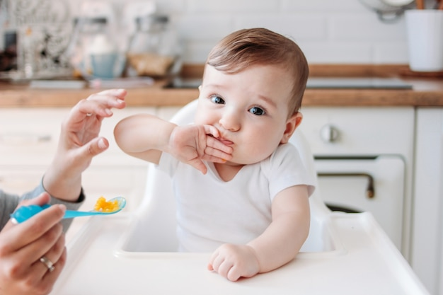 Charming little baby boy eating first food pumpkin from spoon at home