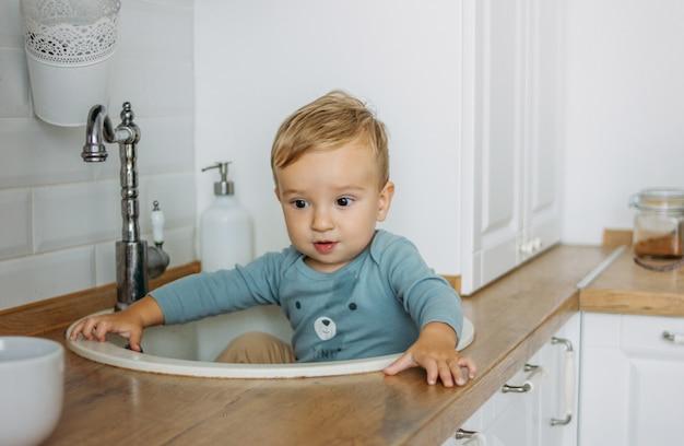 自宅の明るいキッチンの流しに座っている魅力的な小さな男の子