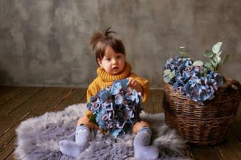 Charming little baby-girl in orange sweater explores blue hydrangeas sitting on warm blanket