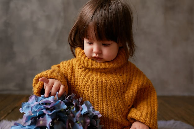 Charming little baby-girl in orange sweater explores blue hydrangeas sitting on warm blanket