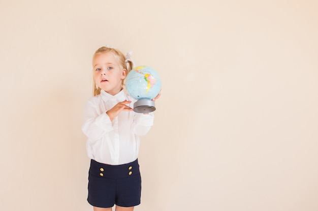 Charming little blonde girl in school uniform is holding a globe