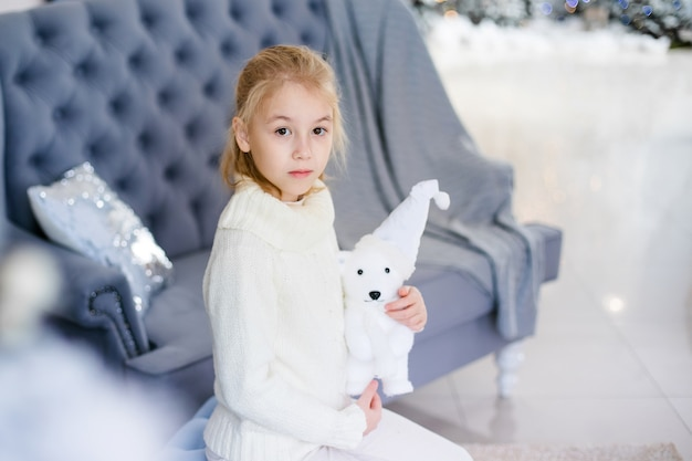 Charming little blonde girl in white warm sweater with toy bear sitting on the blue armchair