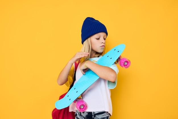 魅力的な小さな金髪の子供の女の子幸せなかわいい子供とスケートボードの子供とバックパック