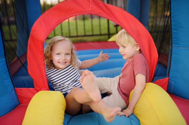 Charming little boy and girl having fun in leisure center for kids.