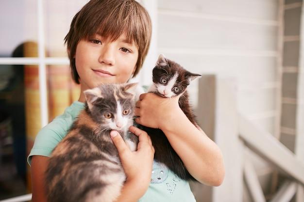 매력적인 소년 그의 팔에 두 고양이를 보유