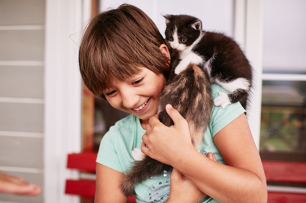 魅力的な小さな男の子は彼の腕の中で2つの子猫を保持します