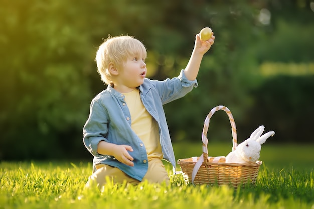 Charming little boy hunting for easter egg in spring park on easter day.