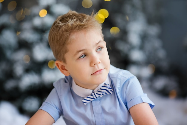 Charming little boy is sitting at home, snowy winter decorated tree on background