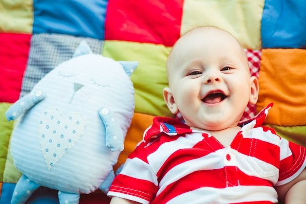 Charming little boy in red stripped shirt lies on the blanket