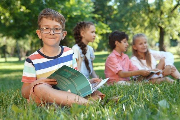 Очаровательный маленький мальчик улыбается вперед, читая книгу, сидя на траве