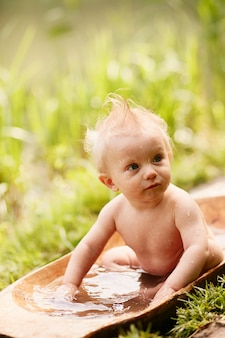 Charming little boy takes a bath on the lawn in green summer park