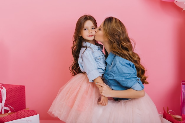 Charming little brunette girl spending time with her young beautiful mom at birthday party. adorable curly woman wearing lush pink skirt kisses daughter with love and holding her hands gently
