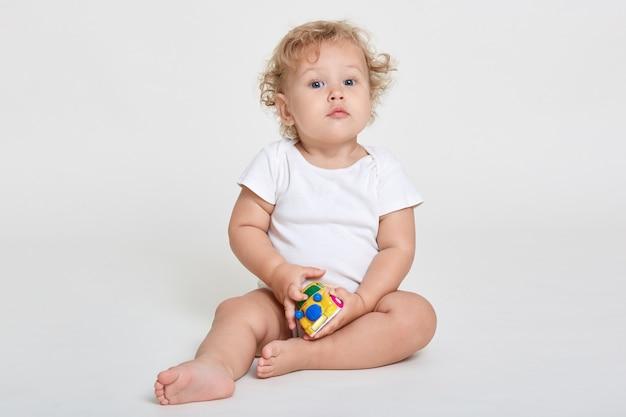Очаровательный маленький ребенок играет с игрушечной машинкой, позируя изолированно над белой стеной с любопытными глазами, в белом боди, любопытный ребенок играет в помещении.