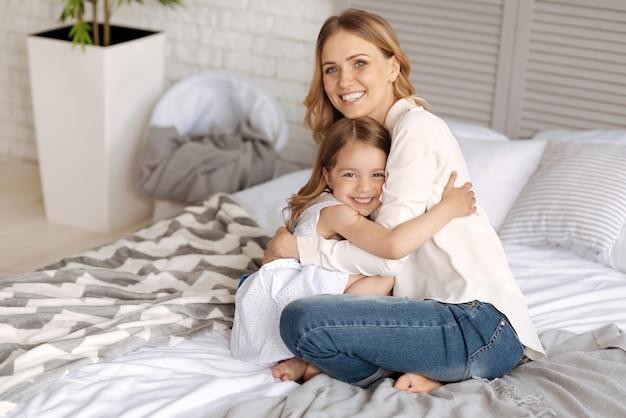 魅力的な小さな娘と彼女の素敵な若い母親がベッドに座って、正面を見て笑顔で抱き合っています