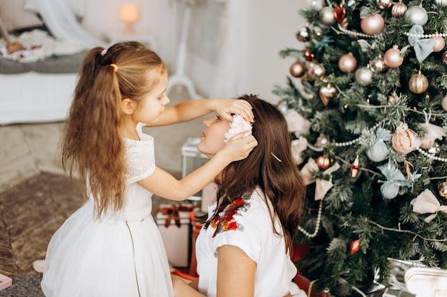 Очаровательная дочурка в красивом платье вложила цветок в волосы матери возле новогодней елки.