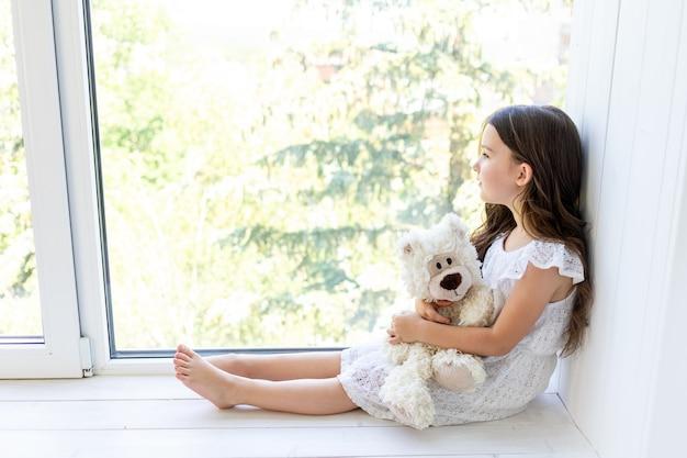 Очаровательная маленькая девочка 5-6 лет обнимает мишку тедди и смотрит в окно